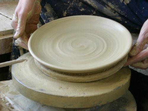 Abheben des gedrehten Tellers von der Töpferscheibe
